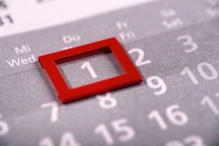 A red frame marks the first day of a month on a calendar Standard-Bild