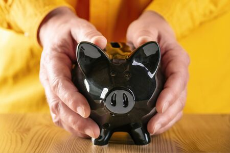 Hands protectively clasp a black piggy bank