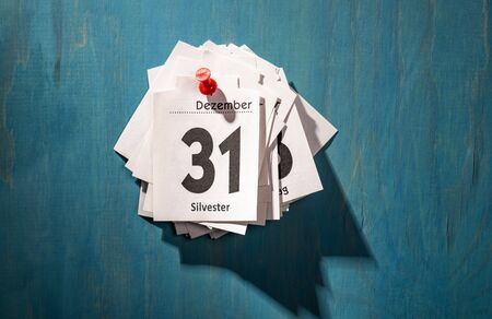 Calendar sheets are pinned to a wall. The top sheet shows the thirty-first of December with the inscription