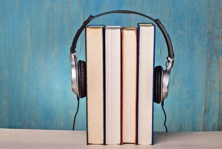 Headphones with four books as symbol for audio books