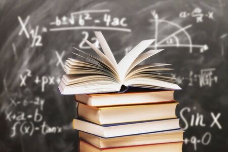 Opened book on a stack in front of a blackboard with mathematical formulas