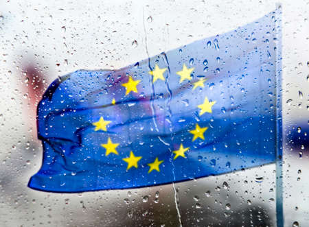European flag behind a glass panel with raindrops
