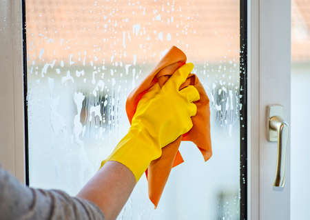 Hand with yellow rubber glove and cloth when cleaning a window