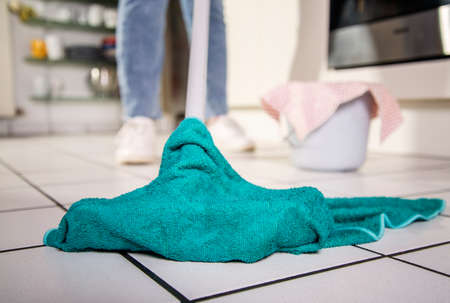 A tiled floor is cleaned with a green cloth