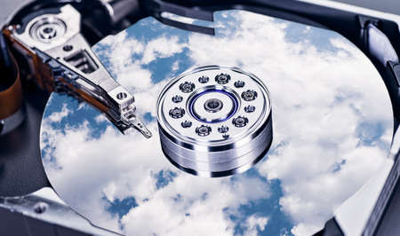 A cloudy sky is reflected on the magnetic disk of a hard drive