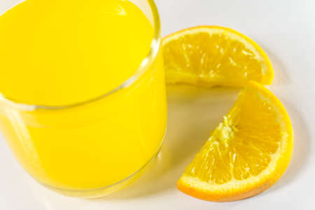 Glass and juicer with freshly squeezed orange juice on isolated on white background