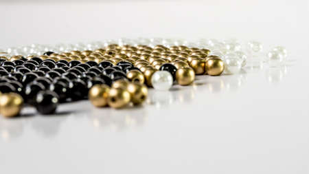 Black, white and gold Beads on white background