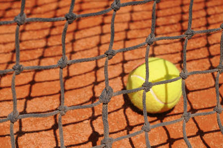 Tennis ball behind the net  photo
