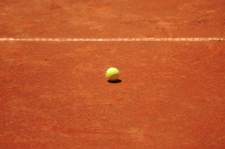 Tennis ball on clay court, daytime  photo
