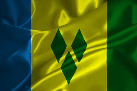 grenadines: St Vincent and Grenadines flag on satin texture. Stock Photo