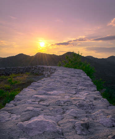leading: Wall leading to breathtaking view of sunset Stock Photo
