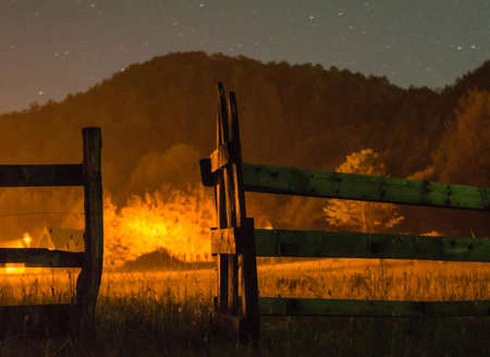 leading light: Wooden gate leading to light at the end of the field