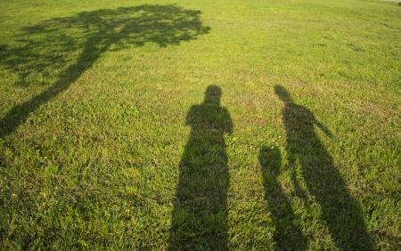 field and sky: familia silueta con las sombras en el campo de hierba Foto de archivo