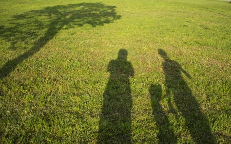 family outdoors: silhouette family with shadows in grass field Stock Photo