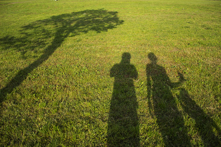 silhouette family with shadows in grass field Stock Photo