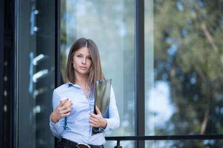 Confident businesswoman holding documents and coffee outside of the office Stock Photo