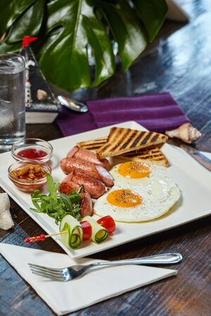 Restaurant breakfast composition image. On a wooden table with a green leaf background Foto de archivo