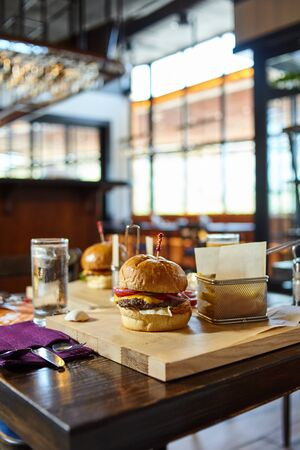 Meal commercial photography - traditional american burgers in restaurant setup. Blurred interior background