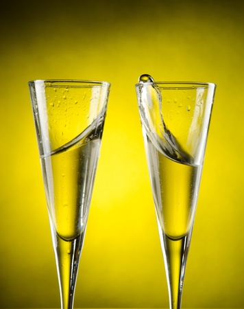 Celebration toast with champagne on yellow background photo