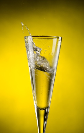 Champagne splashing with yellow background photo