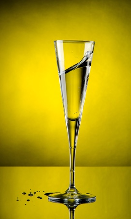 Glass of champagne with yellow background photo