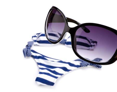 Sunglasses and bikini isolated on white photo