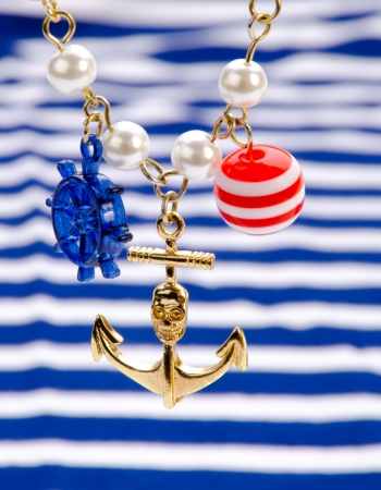 Gold anchor with blue-white striped background photo