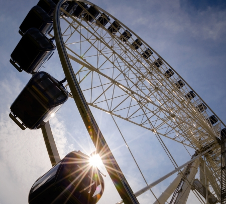 Big ferris wheel with sunbeam and cloudy sky