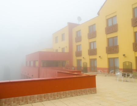 Hotel building with balkony in fog  photo
