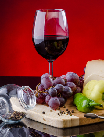 Glass of red wine with grape and vegetables on wood tray photo