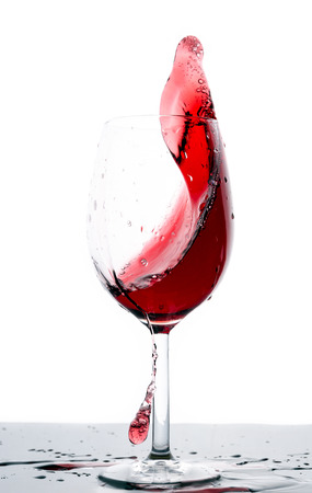 Splashing red wine in a glass isolated photo