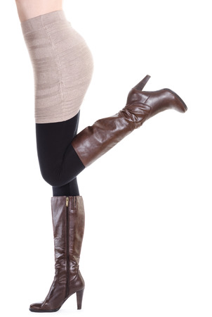 Sexy woman in brown boots - moving up - isolated on white photo