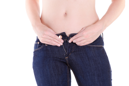 fully unbuttoned: Woman pull up jeans with white background