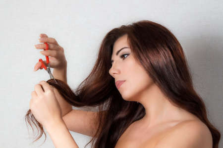 Brunette girl with a pair of scissors cuts hair