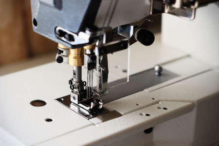Industrial flat-seam sewing machine. Close-up. Soft focus Stock Photo