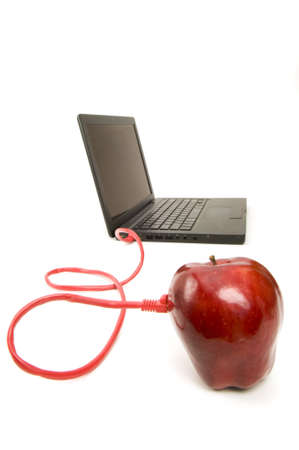 Red Apple connected to a laptop with an ethernet cable Stock Photo
