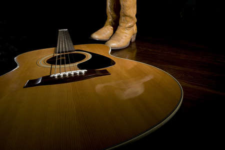 Selective focus on the guitar in the foreground with cowboy boots in the background Stock Photo - 17857670