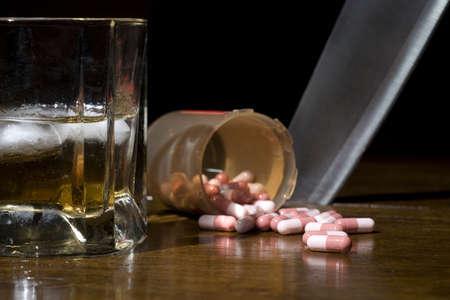 Alcohol en pillen in de voorgrond met een mes steekt de tabel in de achtergrond