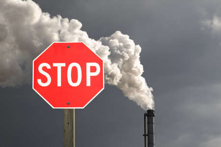Stop sign in front of smokestack pollution with dark cloud in the background photo