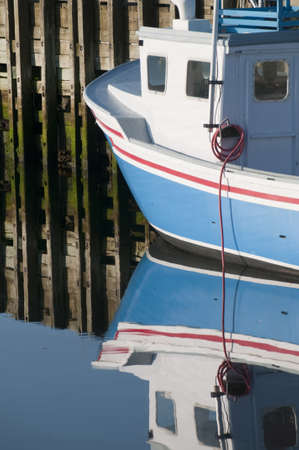 lobster boat: Portion of lobster boat reflection in the early morning harbour area