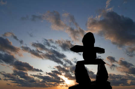 canada aboriginal: Selective focus on the Inukshuk silhouette in the foreground with sunset in the background