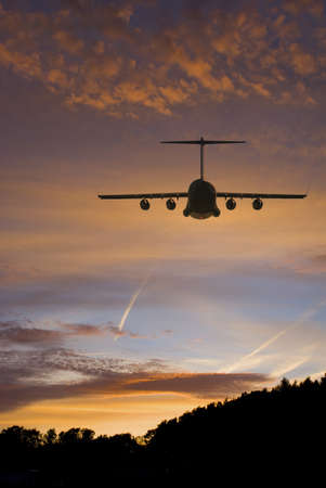 Military transport plane flies over the tree line with brilliant sunset in the background photo
