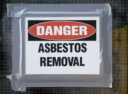 hazmat: Danger Asbestos Removal Sign posted on school window. Stock Photo