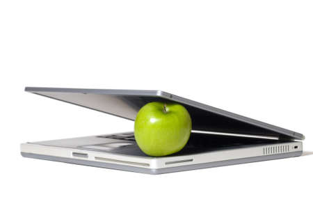 Laptop closing on a green apple - selective focus on the apple. Stock Photo