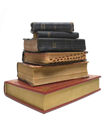 New bible sitting below a stack of antique bibles Stock Photo