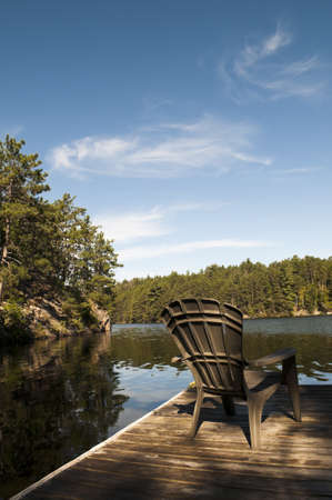 Holiday at the cottage with the sunlight hitting the chair on the dock with lake and shoreline in the background