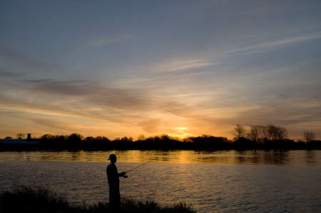 Man fishing from the rivers edge at sunrise