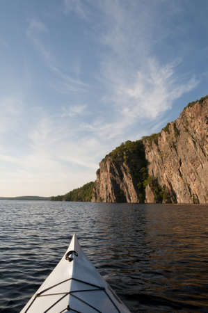 sun drenched: Bow of the kayak in the foreground with the sun drenched Bon Echo cliff is in northern Ontario