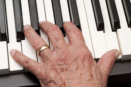 Hand of an older man playing the piano
