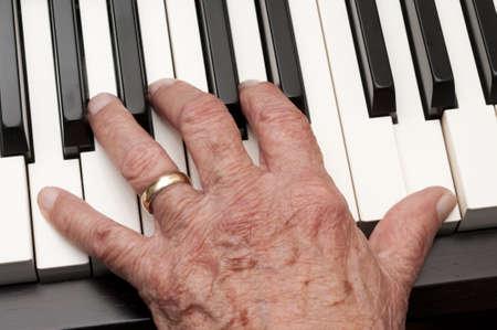 Hand van een oudere man het spelen van de piano Stockfoto